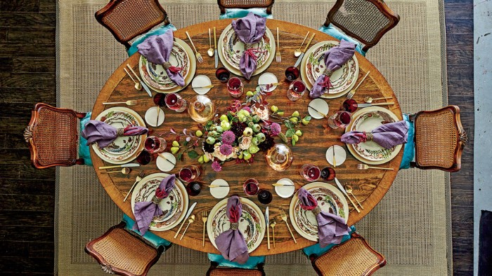 areal shot of an oval wooden table, with eight chairs, and eight ornamental plates, with folded violet napkins, large bouquet in the center of the table