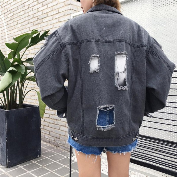 back view of an oversized, grey denim jacket, with three large ripped holes, 90s grunge fashion, worn by a slim woman