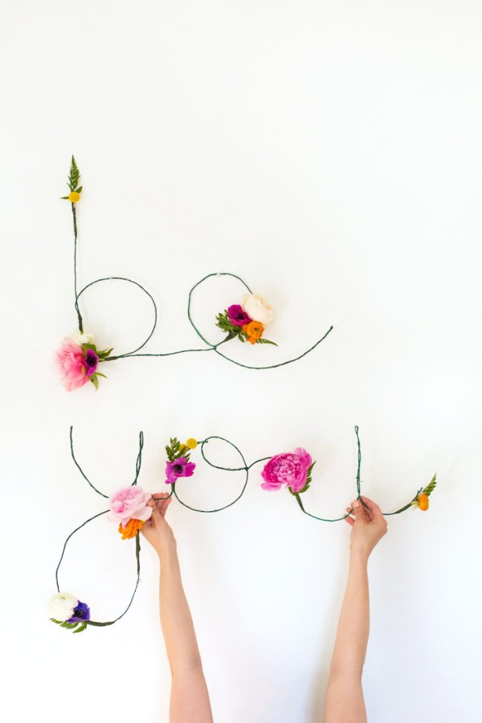 hands holding the word you, made from thin, green wire, and decorated with faux flowers, in different colors, diys for girls, the word be, created in a similar way, is mounted on the wall above