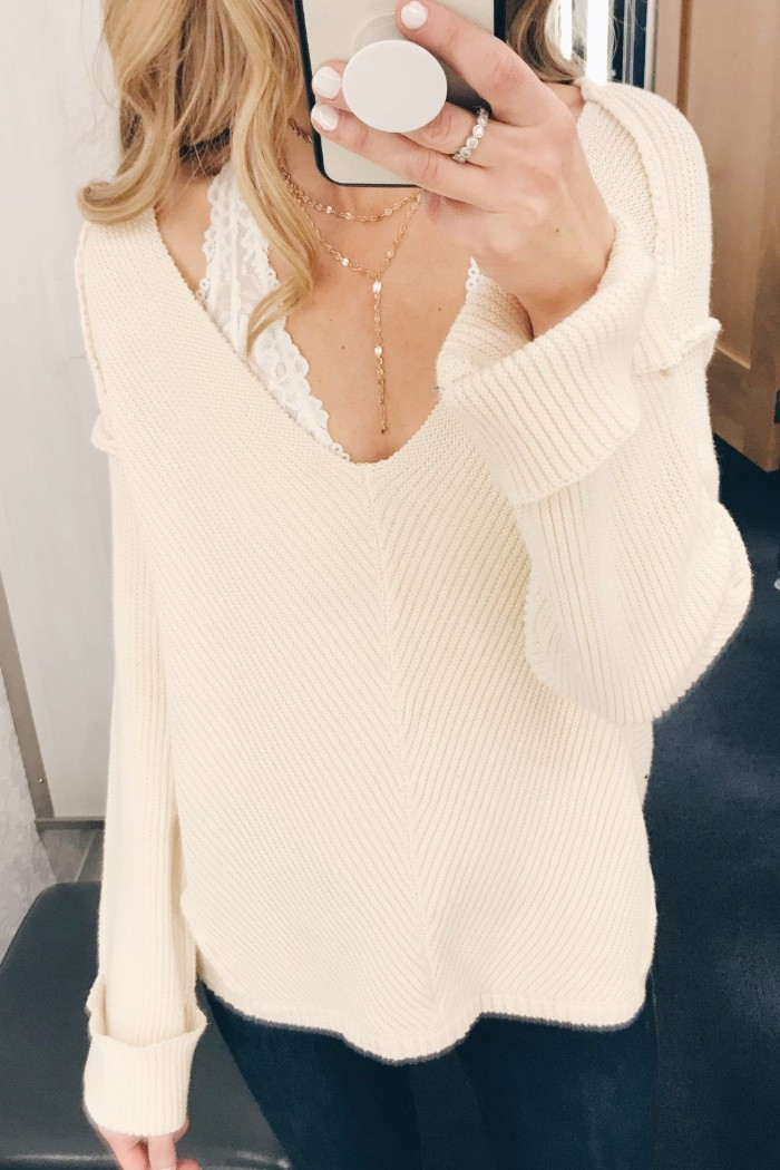 long and soft, pale powder pink v-neck sweater, worn over a white lace bralette, by a slim blonde woman, how to wear a bralette, dark blue skinny jeans
