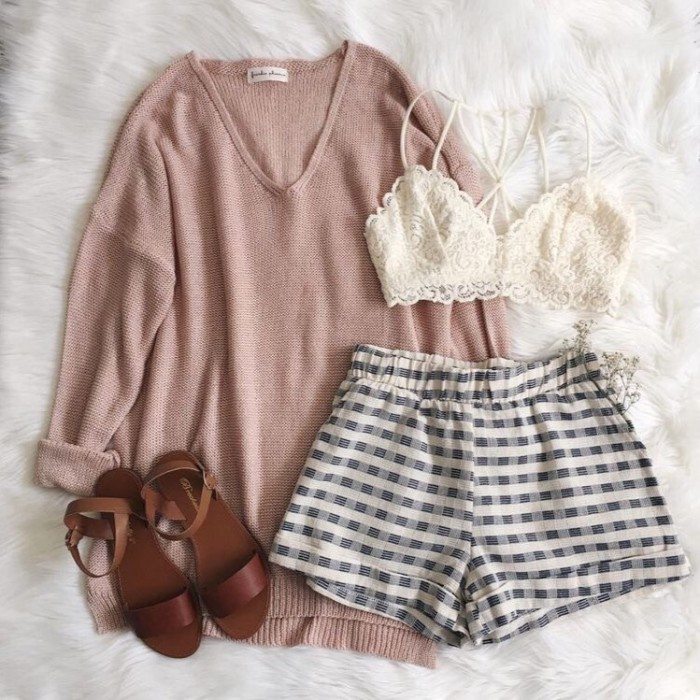 checkered shorts in black and white, an oversized powder pink v-neck jumper, light pink lace bralette, and a pair of brown, flat leather sandals, what to wear with a bralette, on a white faux fur surface