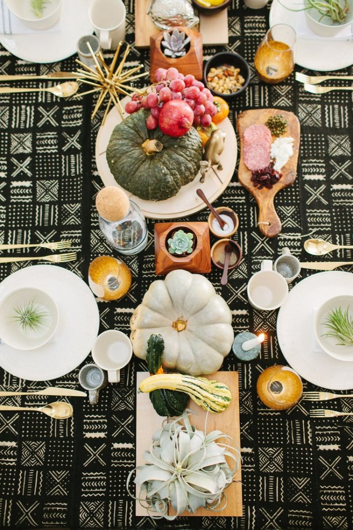 pomegranates and grapes, pumpkins and gourds, decorating a thanksgiving table, covered with a black and white, patterned tablecloth with plates, cutlery and glasses