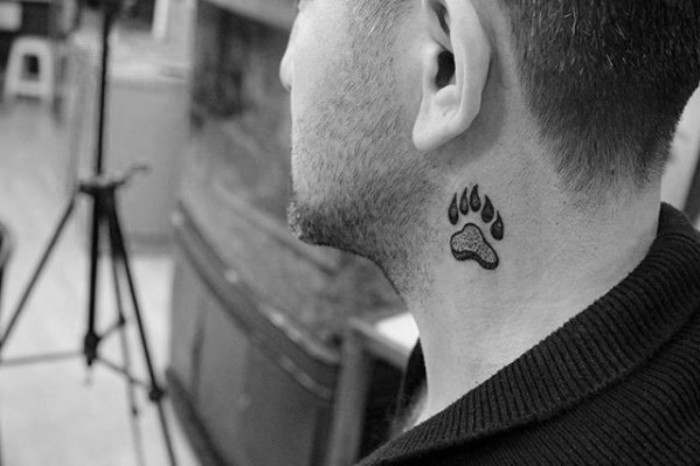 small symbolic tattoos, paw print with claws, tattooed in black, on the side of a man's neck, signifying strength and bravery