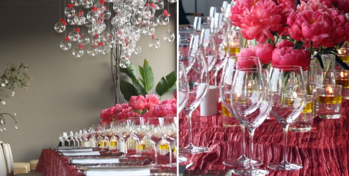pink peonies and multiple wine glasses, on a table set for a festive meal, with a dark pink tablecloth, and multiple crystal baubles, with pink bows hanging overhead
