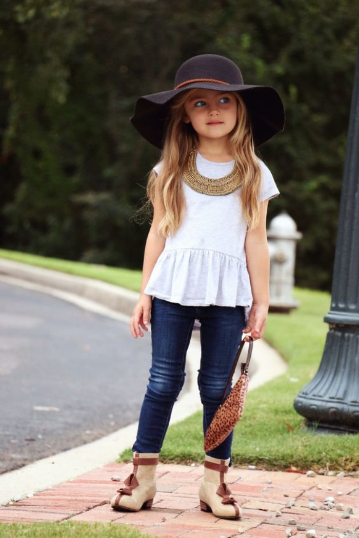 wide-brimmed black felt hat, worn by a child, with long wavy blonde hair, white peplum top, and blue skinny jeans, girls thanksgiving outfit, beige and brown ankle boots