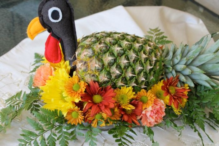 felt turkey head, attached to a pineapple, decorated with yellow, pink and orange flowers, and green fern leaves, creative turkey decorations
