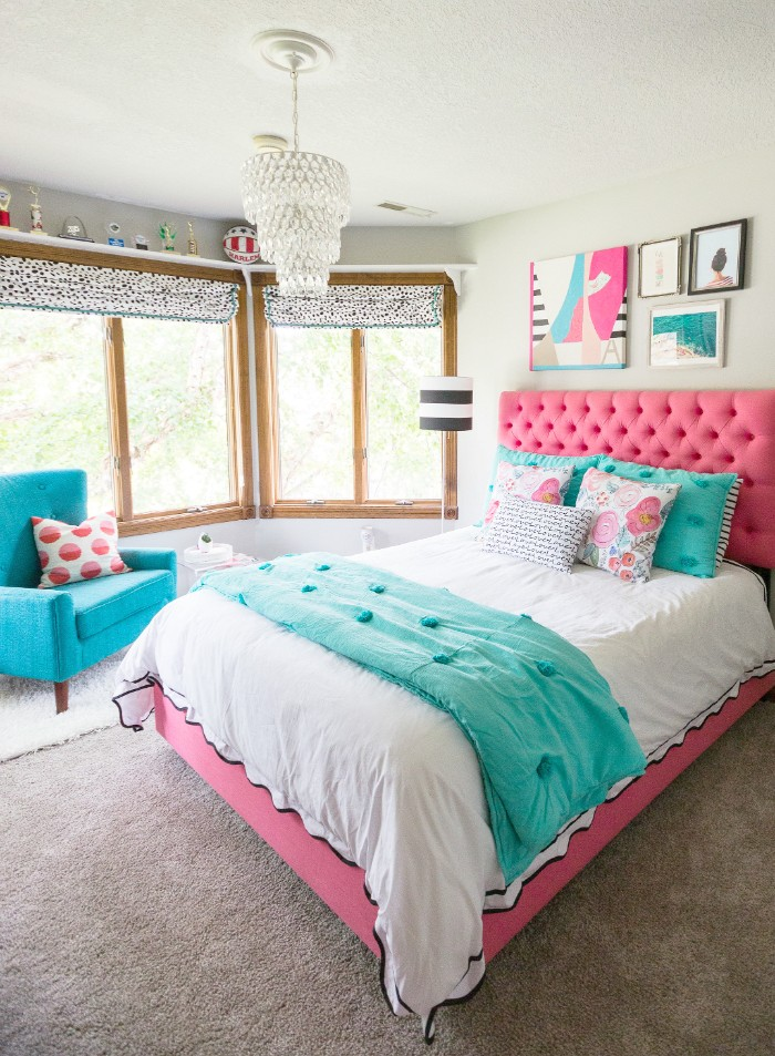 soft headboard in pink, on a pink bed, with white and teal covers, and five cushions, in teal and white and multicolor, two large windows, and wall decorations