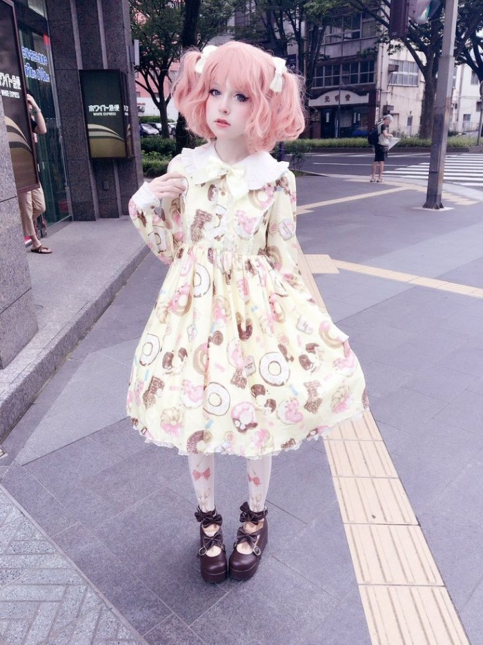 short pink wig, featuring pigtails decorated with white bows, on a pale girl, dressed in a cream dress, with a frilly white collar, and a pattern with colorful donuts and sweets