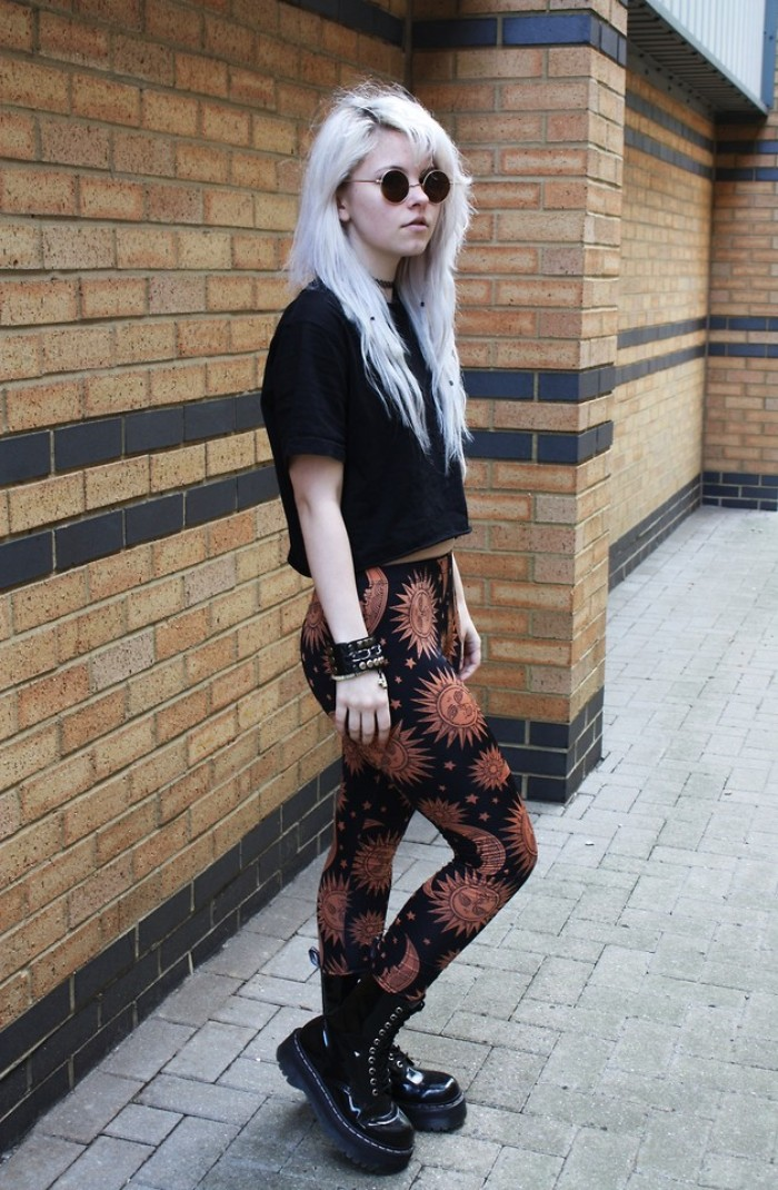 patterned leggings in black and beige, featuring suns and moons, worn with a black cropped t-shirt, and black patent leather combat boots, by a young grunge girl, with platinum blonde hair, dark roots and round sunglasses