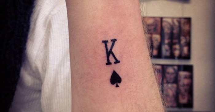 king of spades symbol, tattooed in black ink, on the arm of a man, lower arm tattoos, seen in close up