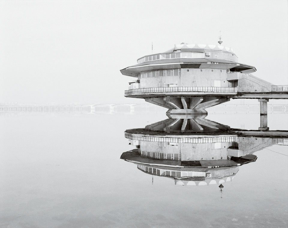 round concrete building, suspended over a lake, poplavok cafe in ukraine, brutalist architecture, seen on a black and white photo