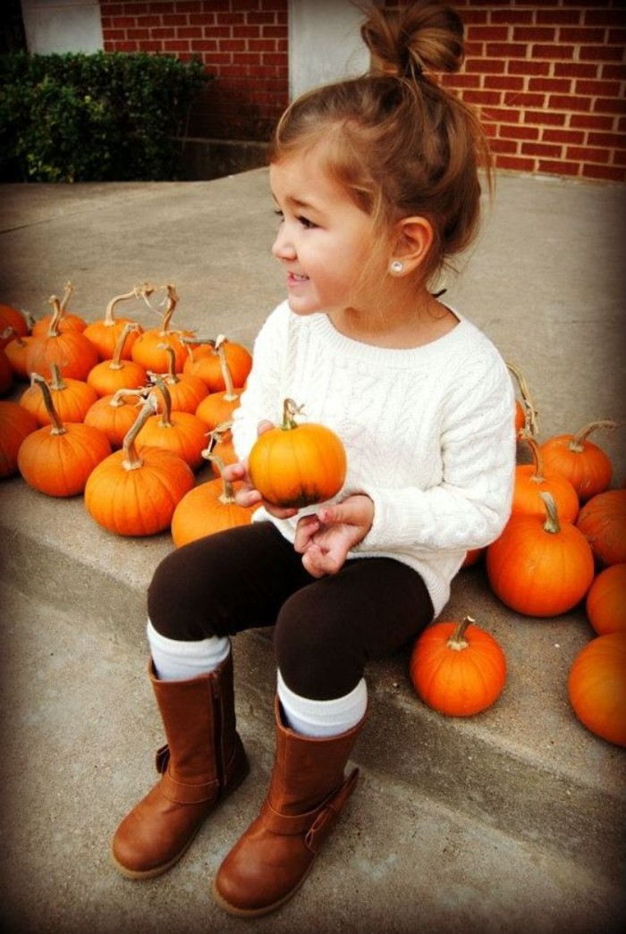 child dressed in a white cable knit jumper, black leggings with white socks, and tall brown leather boots, smiling while holding a small pumpkin, toddler thanksgiving outfit, more pumpkins nearby