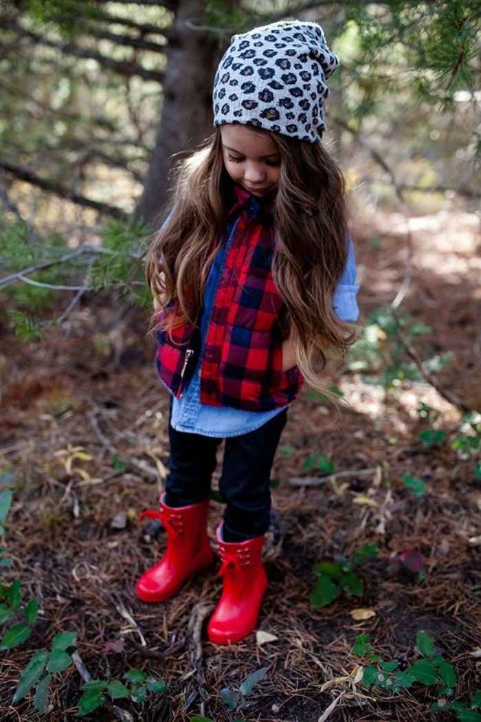 rubber rain boots in red, worn by a small girl, with dark blue jeans, a light chambray, a plaid red and blue gilet, and an animal print beanie hat, toddler thanksgiving outfit