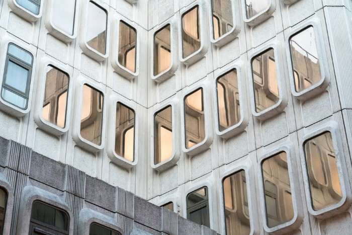 close up of a building, made of grey concrete, brutalism, featuring multiple rectangular windows, with rounded edges, covered in reflective glass