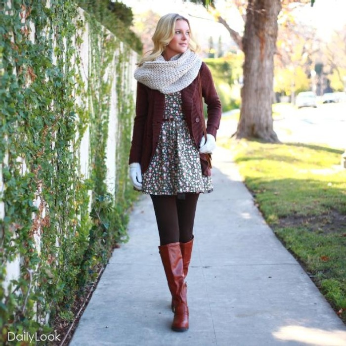 chunky knit off-white scarf, worn over a brown cardigan, and a ditsy mini dress, by a blonde young woman, thanksgiving outfits for women, tall dark red leather boots