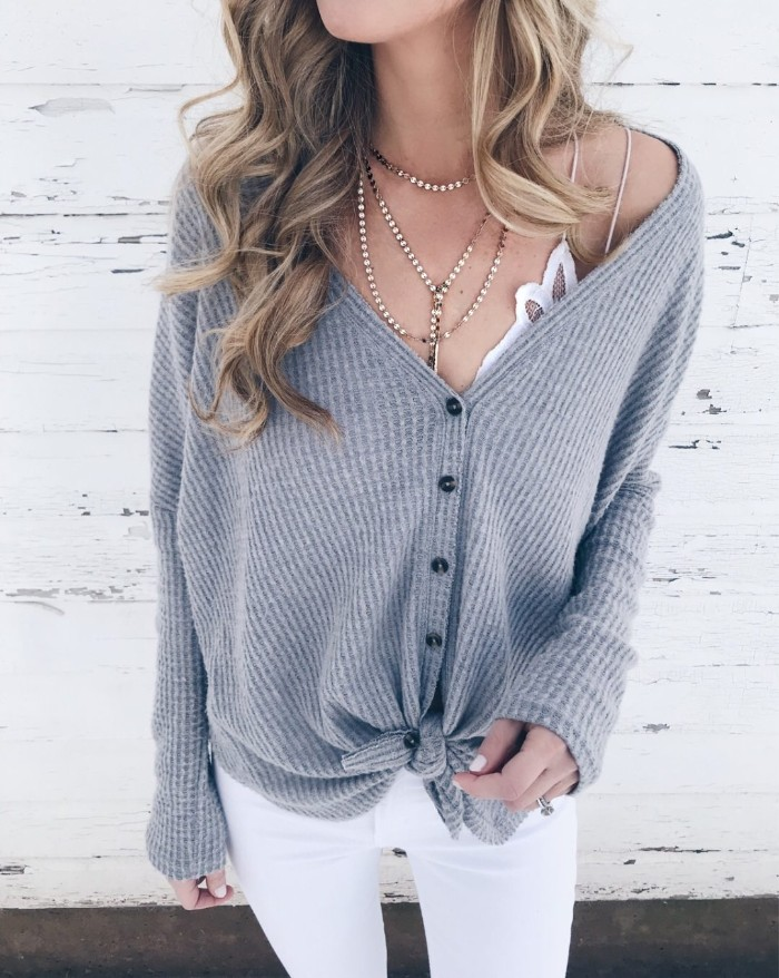 skinny trousers in white, and a white bralette, worn with a grey ribbed cardigan, tied in a knot at the bottom, what is a bralette, on a slim blonde woman, with wavy hair