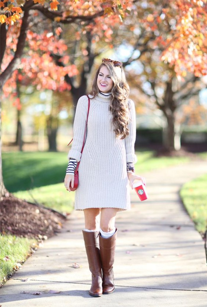 off-white sweater dress, worn over a black and white, striped polo neck jumper, comfy outfits, on a smiling brunette woman, with tall brown leather boots