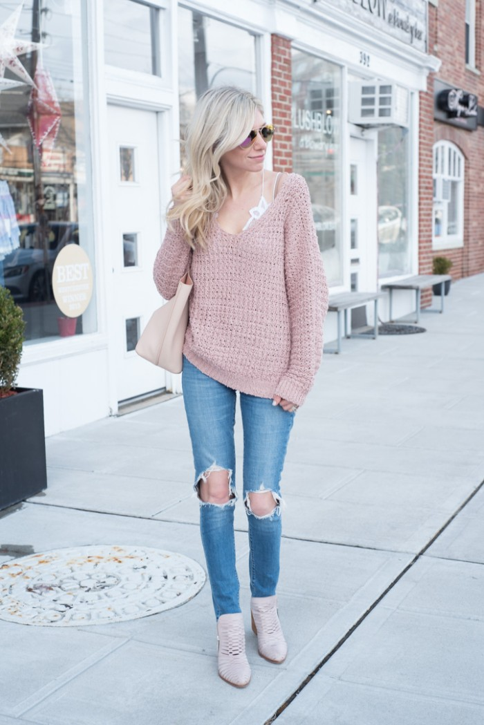 platinum blonde woman, dressed in ripped skinny jeans, a baggy pastel pink, chunky knit jumper, and a white lace bralette, what to wear with a bralette, light grey suede ankle boots