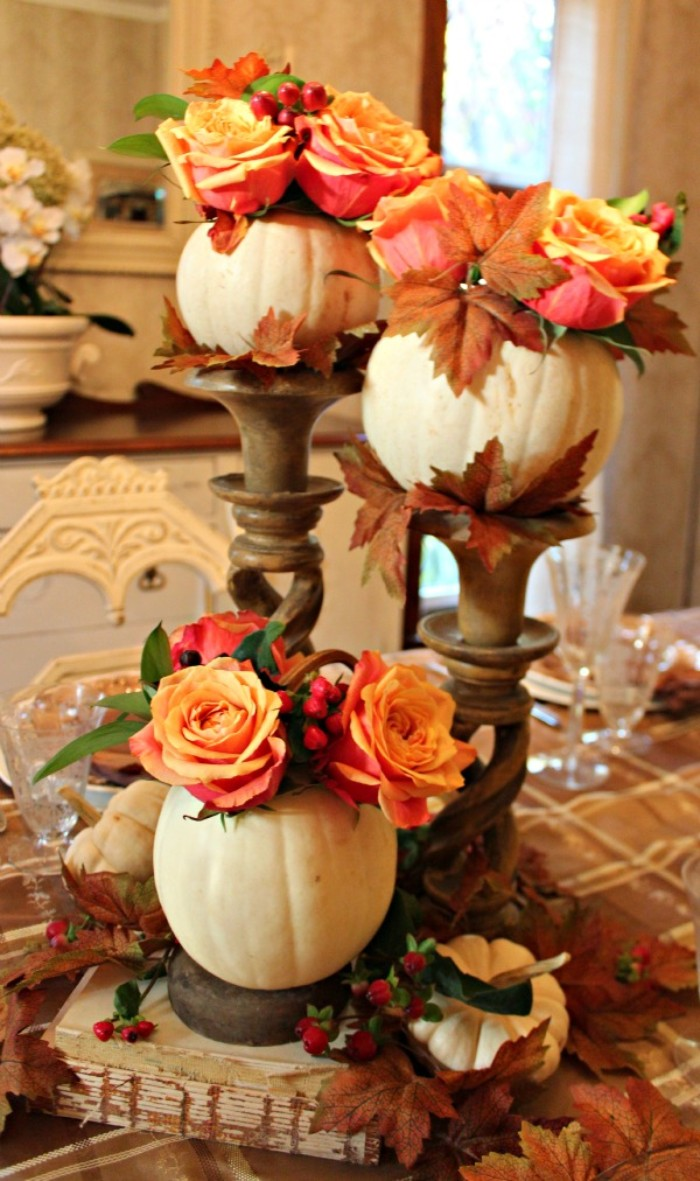 three small hollow white pumpkins, filled with orange roses, and brown fall leaves, and placed on ornamental stands