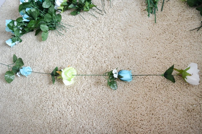 four fake flowers, with pale blue, light yellow and white blossoms, and long green stems, stuck together to form a column, diys for girls, more blue flowers in the background
