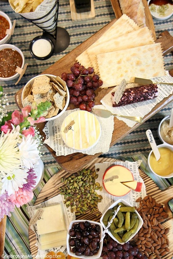 50th birthday themes, wine tasting experience, wooden boards containing different kinds of cheese, crackers and grapes, olives and pickles, on a table decorated with flowers
