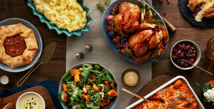assorted dishes including two roasted chickens, muashed potato and salad, thanksgiving text messages, on a wooden table
