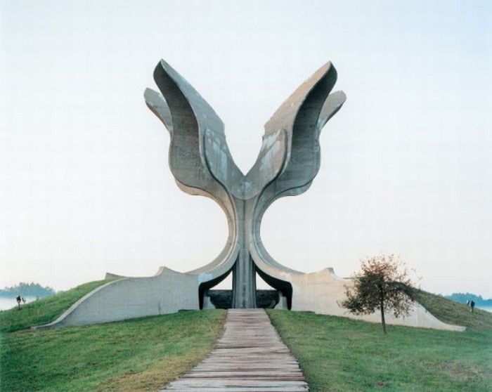 wing-shaped concrete monument, in jasenovac croatia, built on a green hill, with a pathway and a small tree