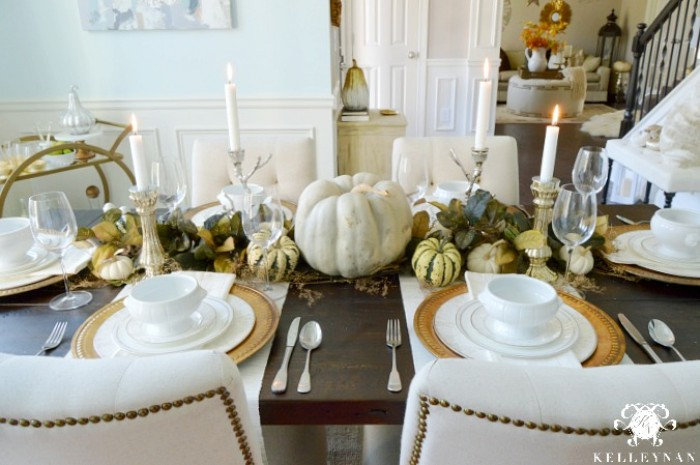 dining room with a dark brown wooden table, decorated with pumpkins, in different sizes and colors, four lit white candles, plates and bowls, napkins and cutlery