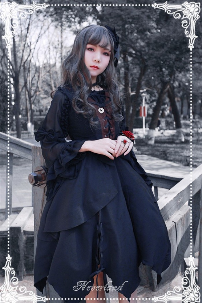serious looking gir, with dark curled hair, dressed in a black, gothic lolita dress, with a lace up detail, and frilly sheer sleeves