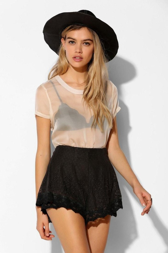 round hat in black, worn by a slim, young blonde woman, dressed in a sheer white t-shirt, over a black bralette, and black lace shorts, bralette outfit, on a white background
