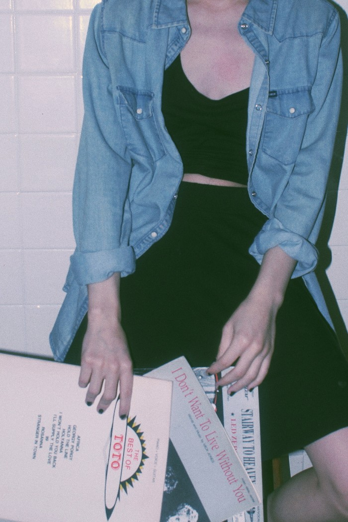 chambray shirt in light blue, worn unbuttoned over a black mini skirt, and a black cropped top, by a pale woman, holding three record cases
