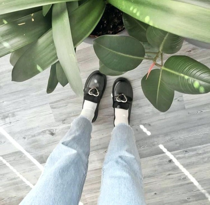 house plants with different, large green leaves, near a pair of legs, dressed in pale blue, acid wash cutoff ankle jeans, worn with white socks, and black loafers, featuring silver heart-shaped buckles, grunge girl