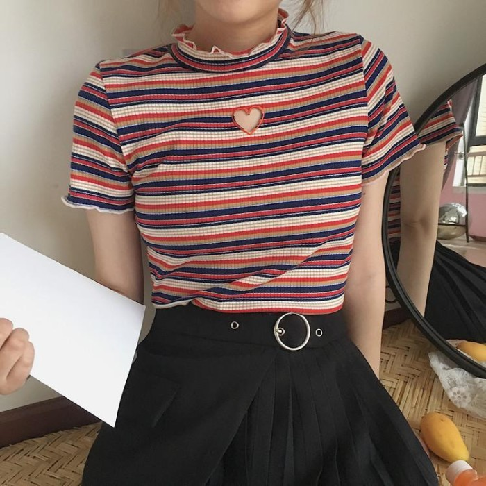 heart-shaped cutout detail, on a striped short-sleeved top, with small frill details on the neck and sleeves, 90s grunge fashion, worn with a belted, pleated black mini skirt