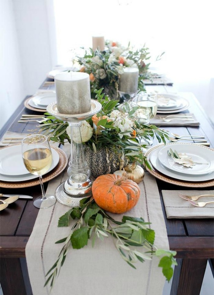 thanksgiving tablescape, dark wooden table, decorated with small orange pumpkins, green leaves and silver candles, on clear glass holders, white and gold plates, one wine glass and silver cutlery