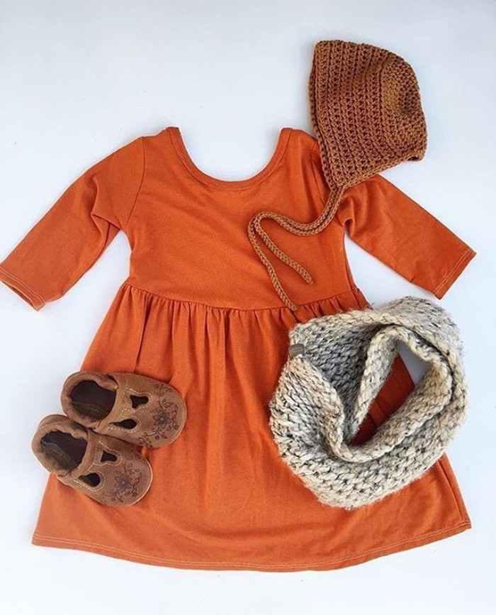 orange jumper dress, with quarter sleeves, toddler thanksgiving outfit, brown suede shoes, an off-white tube scarf, and a brown knitted hat