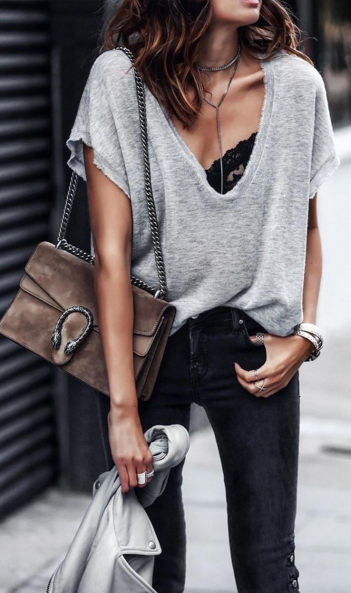 baggy pale grey v-neck t-shirt, worn over a black lace bralette, with dark grey skinny jeans, how to wear a bralette, on a brunette woman, carrying a pale brown, suede shoulder bag