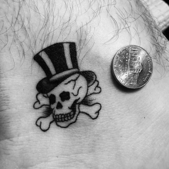 small tattoos with meaning, a skull with a top hat, tattooed in black, on a man's ankle, penny placed next to it for scale, memento mori