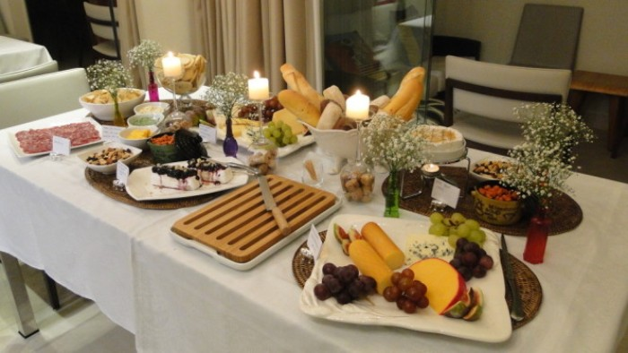 bread basket and a cheese platter, plates with salami and other nibbles, on a table decorated with several small white bouquets, and three lit candles, 50th birthday themes, hosting a wine tasting