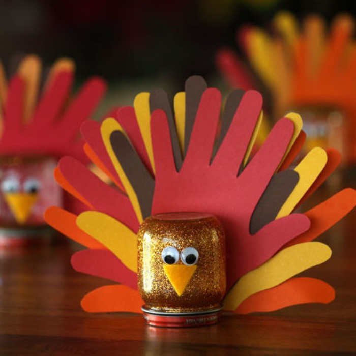 kids diy turkey decorations, small mason jar filled with gold glitter, decorated with eye stickers, a small felt beak, and a tail, made from hand-shaped paper cutouts in different colors