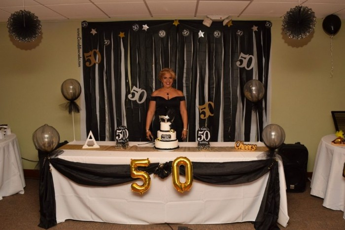 Blonde Woman In A Black Dress Smiling While Standing Next To Festively Decorated Table Creative 50th Birthday Party Ideas
