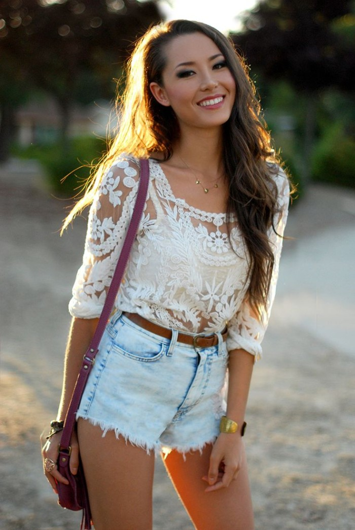 young brunette woman, dressed in pale blue denim cutoff shorts, a white bralette, and a white, see-through embroidered top, how to wear a bralette, small purple shoulder bag
