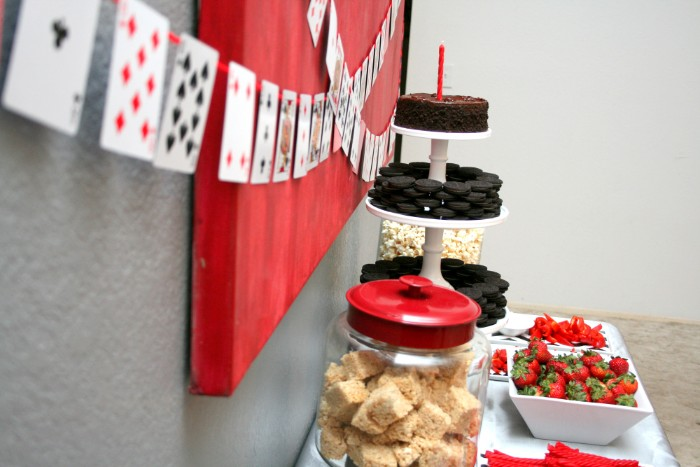 strawberries and cookies, cakes and popocorn, in dishes and glass containers, placed on a table, near a wall, decorated with diy playing card garlands, 50th birthday party ideas for men, easy and cheap