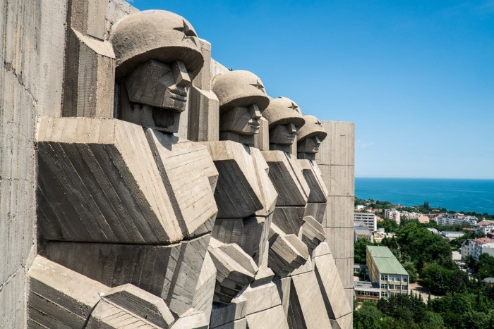 brutalist design of a monument, featuring four soldiers, with helmets decorated with stars, a city near the sea, visible in the background