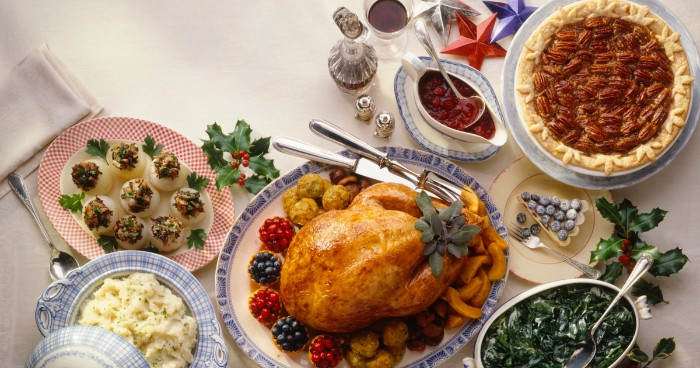 happy thanksgiving wishes, a table with several dishes, a roasted turkey, devilled eggs and mashed potato, spinach salad and pie