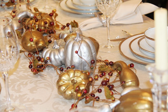berries in yellow and dark red, and gold and silver, spray-painted pumpkins and gourds, decorating a pale cream ornamental tablecloth, with glasses and gold-rimmed stacked plates