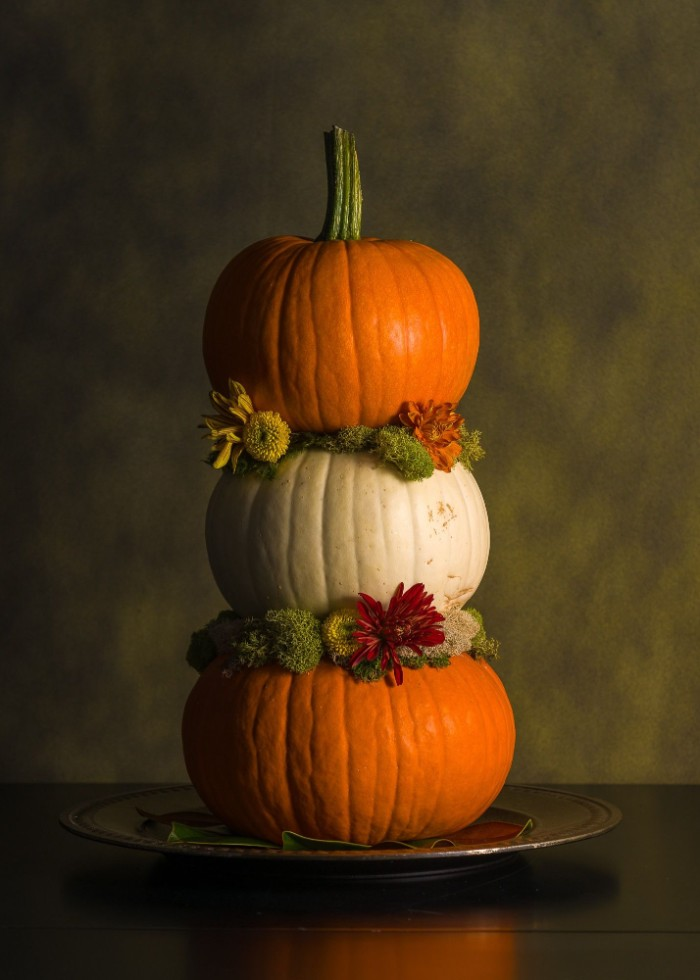 tower-like thanksgiving ornament, made from three orange and white stacked pumpkins, decorated with red and yellow flowers, and light green plants