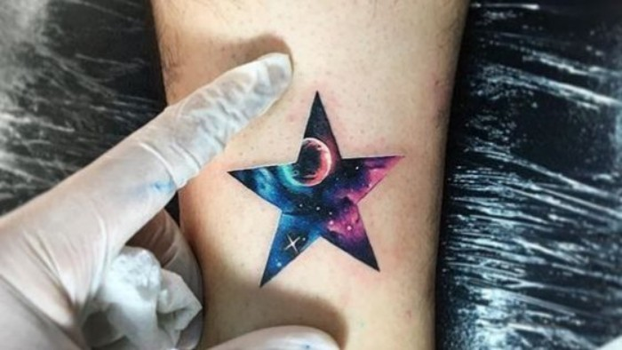 star shape containing a drawing of a starry sky, with a planet, and some purple and light blue nebulae, tattoed on a person's arm, forearm tattoos