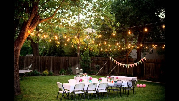 trees decorated with string lights, and a colorful banner, near two tables, set up for a festive meal, 50th birthday party ideas for mom, pink balloons in a garden