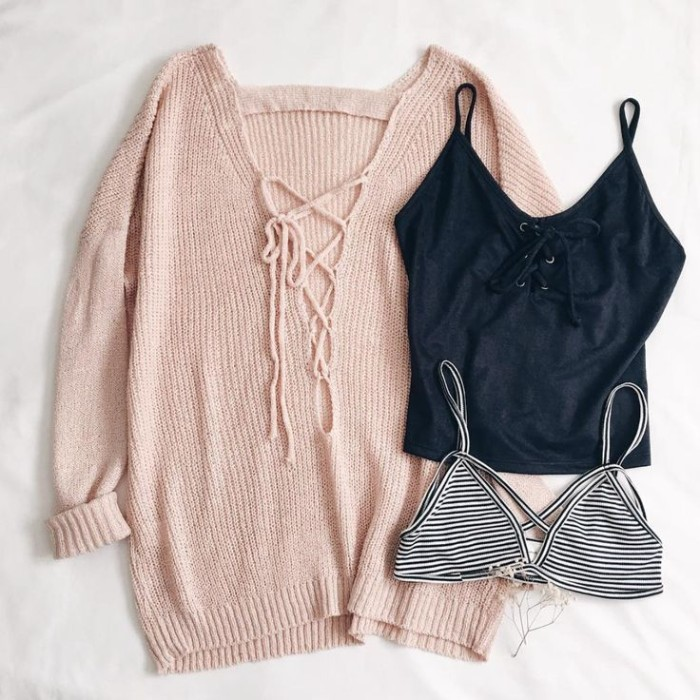 three garments placed on a white surface, a pale pastel pink oversized jumper, with a lace-up detail, a striped black and white bralette, and a black lace-up tank top, outfits with bralettes