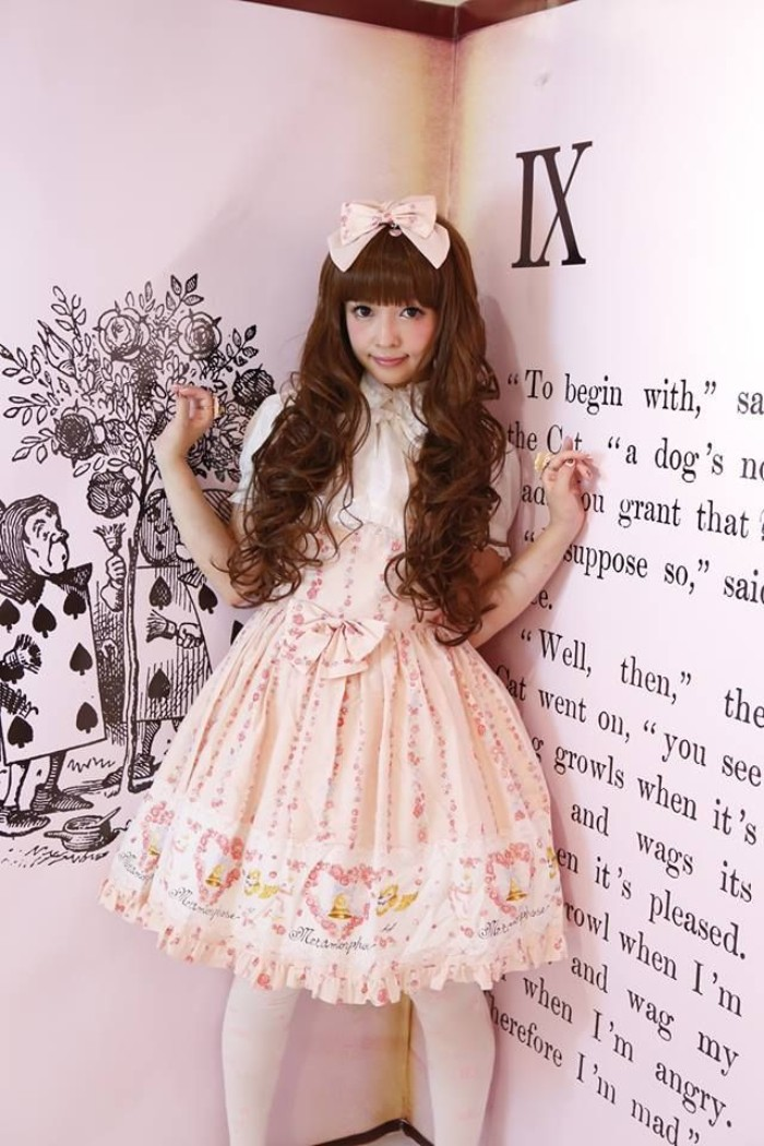 giant book behind a girl, in a long curled brunette wig, with straight bangs, wearing a light peach pink and white dress, with cutesy print, frills and bows, sweet lolita